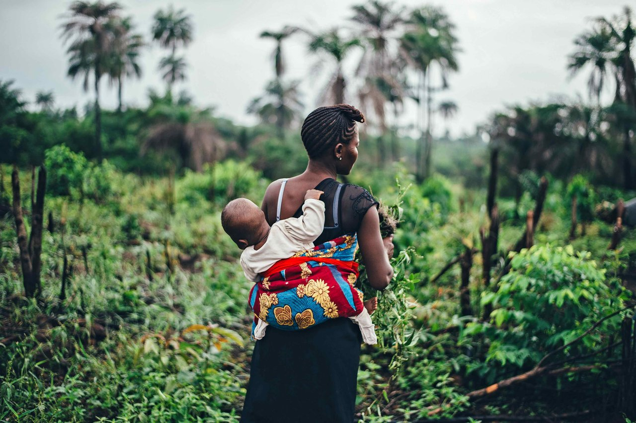 Woman farmer, carrying a baby